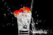 splash in a glass with three red berry and ice on a black backgr