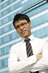 Asian business exec standing in front of an office building