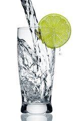 Water flowing in a glass with a lemon segment