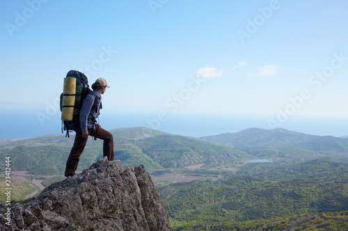 Backpacker girl standing on a high rock