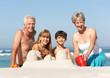 Grandparents And Grandchildren Building Sandcastles Together On