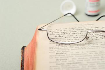 Buch mit Globuli und Brille