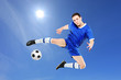 Soccer player with a ball in action against blue sky
