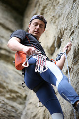 Rock climber going to fix quickdraw to rock