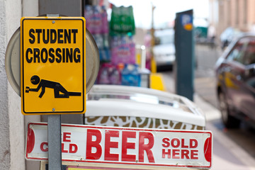 """Warning signs """"Drunken students crossing"""" and """"Beer sold here"""""""