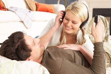 Couple Listening To MP3 Player On Headphones Relaxing Laying On