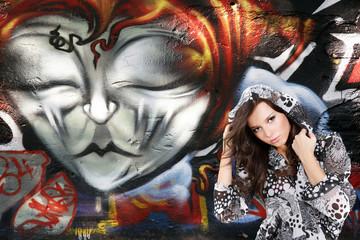 beautiful woman on  urban graffiti wall background
