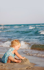 cute toddler girl playing on beach