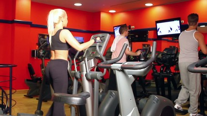 Beautiful sporty woman is exercising at the gym centre
