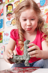 Child  moulding from clay in play room.