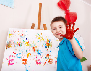 Child painting on easel by hands.