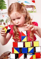 Child preschooler play block in play room.