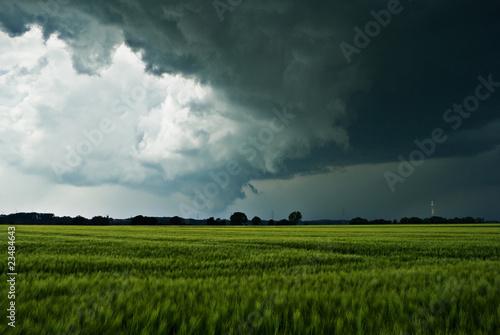 Leinwandbild Motiv Sturmwolken über einem Feld