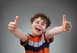 Boy showing OK sign on gray background