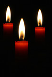 Three blazing candles on a black background poster