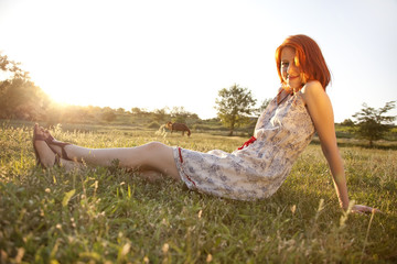 red-haired girl in the village at sunset