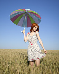 Girl with umbrella at wheat field