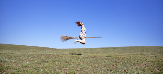 young witch flying over field