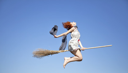 Young witch with broom flying in sky