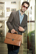 Confident young businessman holding a briefcase