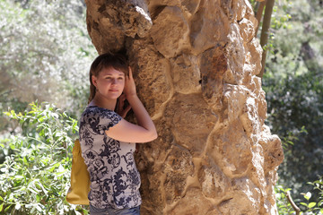 Girl poses with rock pillar at park Guell