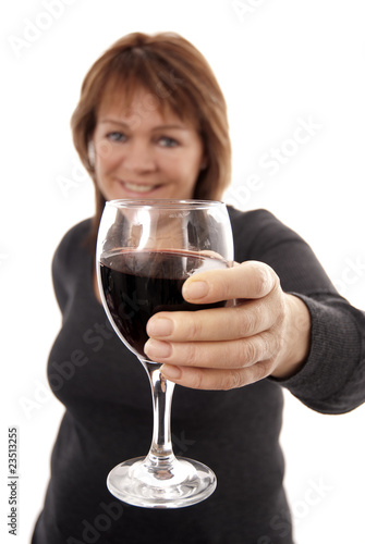 Woman holding out glass of red wine