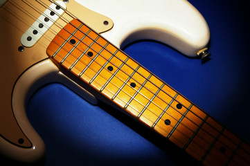 closeup of an electric guitar on blue