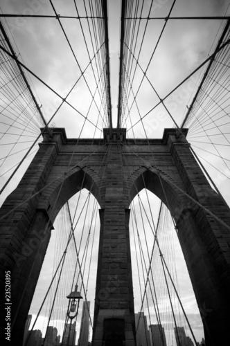 Black and white upward view of Brooklyn Bridge - 23520895