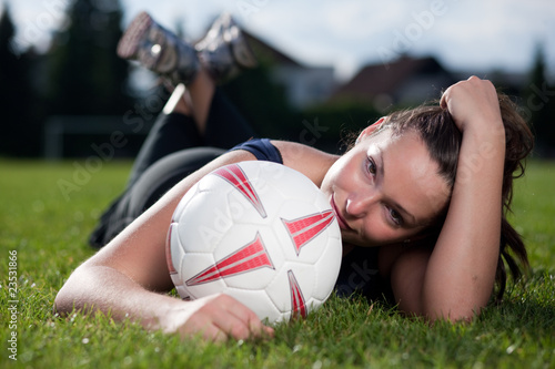 Cute girl lying on a football field