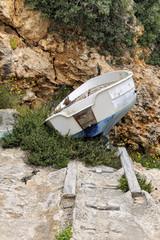 Small fishing boat abandoned near a dry slipway in Cala Pi