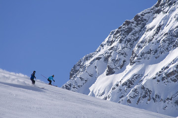 Two skiers in front of a large snowy mountain
