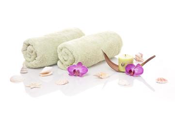 Handtücher, Kerze, Orchideenblüten und Muscheln