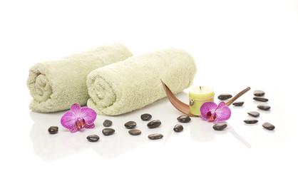 Handtücher, Kerze, Orchideenblüten und Steine