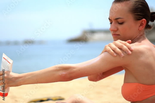 Woman on the beach applying lotion
