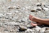 feet in sun on stone beach poster