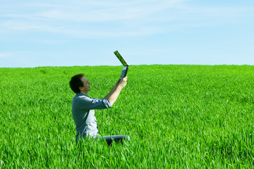 young man uses a laptop in the green field