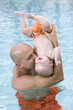 Loving father and baby having fun in swimming pool