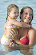Mother and little girl in swimming pool