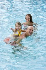 Family with young child playing in swimming pool