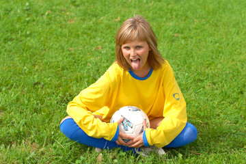 wilful sport girl is siting on the grass with soccer ball
