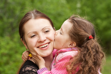 The small daughter kisses mum