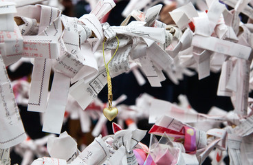 Japanese paper omikuji fortunes and a heart charm