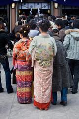 Japanese women in kimono wait to pray at a shrine