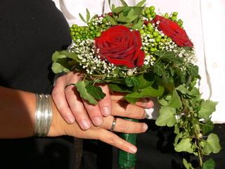 Hände mit Brautstrauß aus roten Rosen