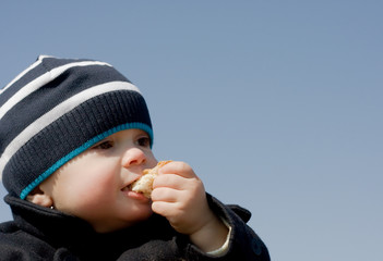Мальчик ест булку на фоне голубого неба
