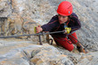 Young female climber with red helmet