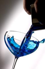 Pour blue liquid into a cocktail glass