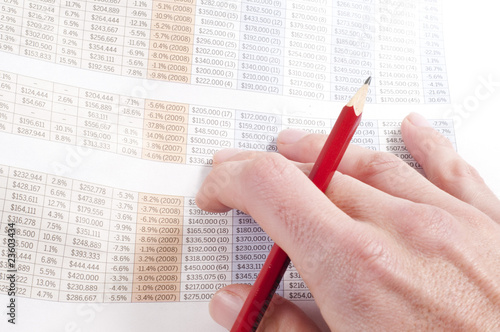 Man working out figures from newspaper holding pencil