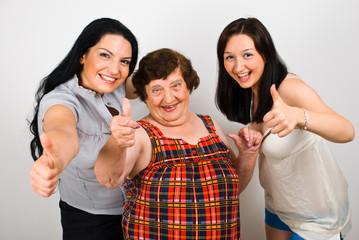 Happy grandma with granddaughters give thumbs