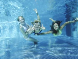 Drei Mädchen tauchen fröhlich im Pool